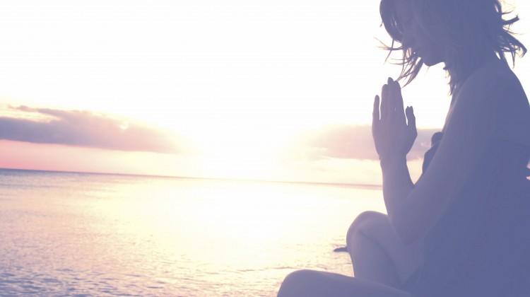 Woman meditating beach sunset