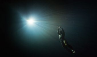 Free diver swimming to the light