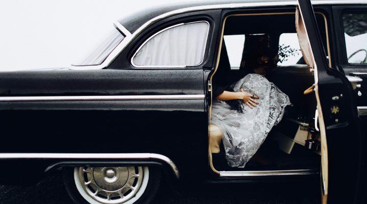 Woman in black vintage car